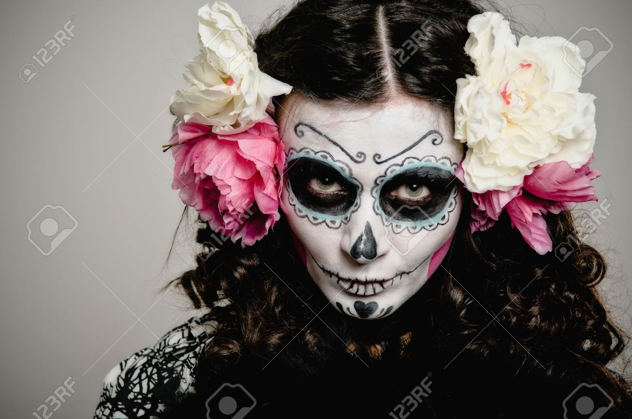 A Woman In Halloween Costume And Skull Makeup Holding Flowers ...