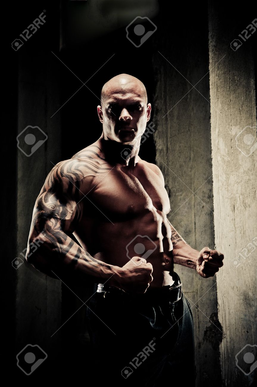 Handsome Fit Bodybuilder Standing Clenching His Fists And Flexing ... for Bodybuilding Photography Lighting  174mzq