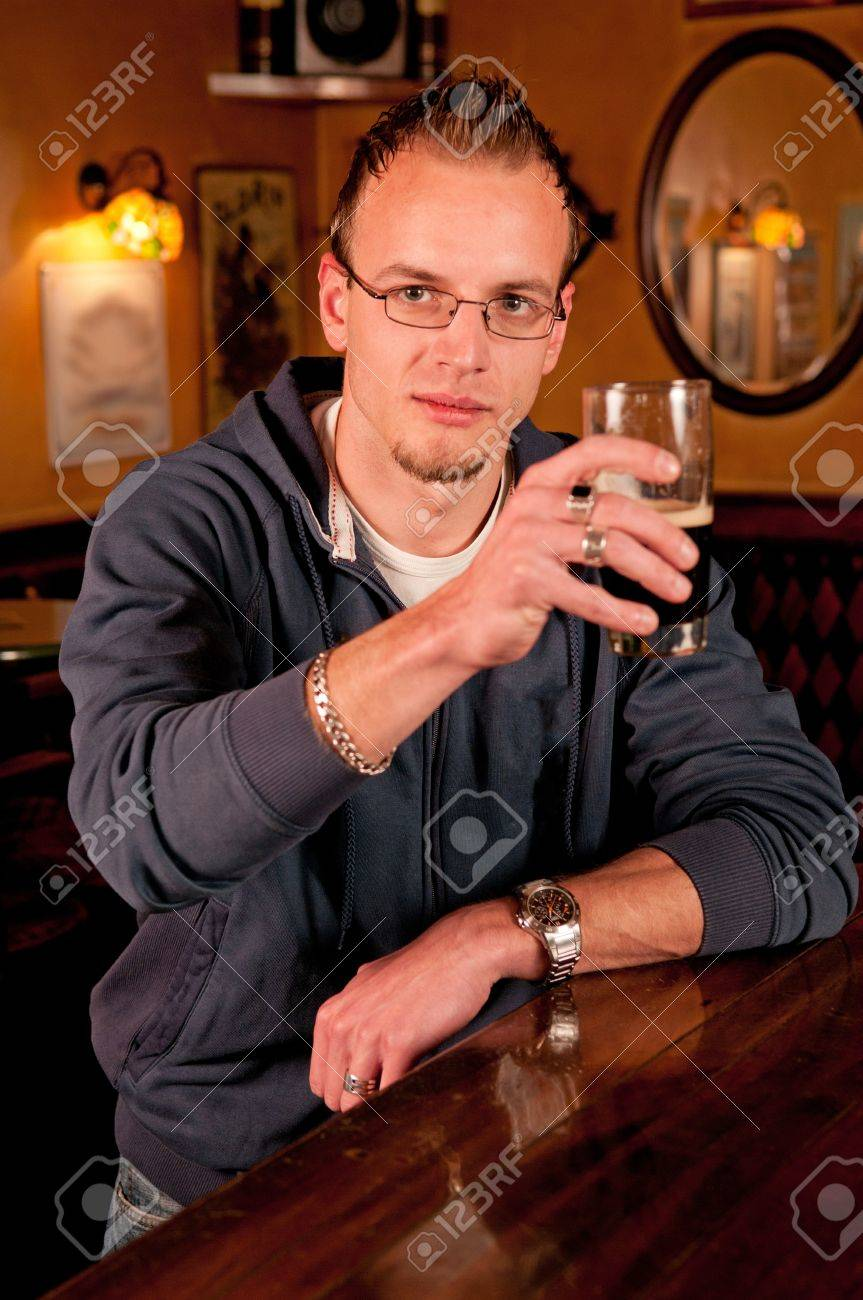 Man with a beer in bar giving a toast and smiling Stock Photo - 13362606