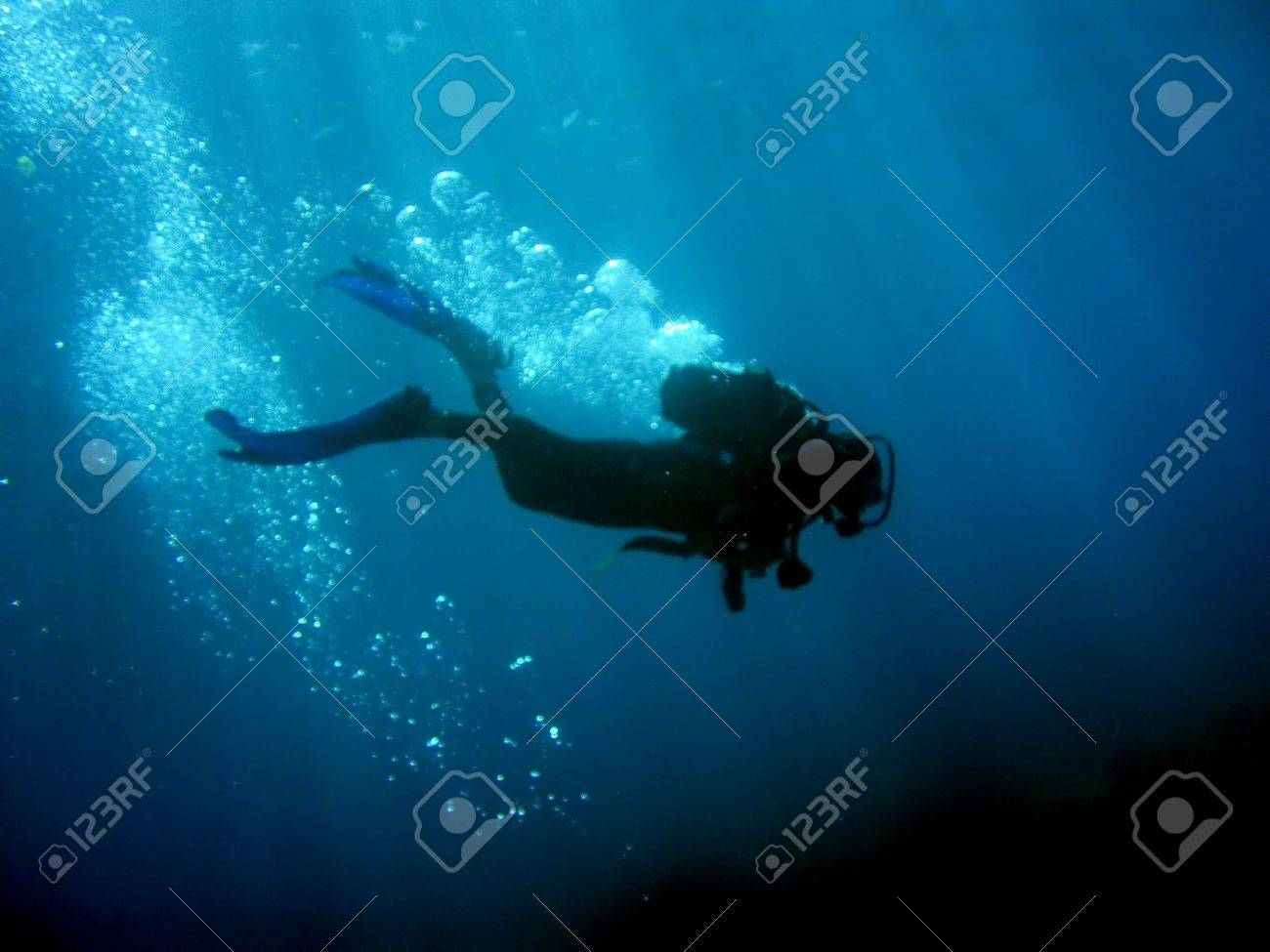 Diver with bubbles and sunrays against black bottom Stock Photo - 9948438