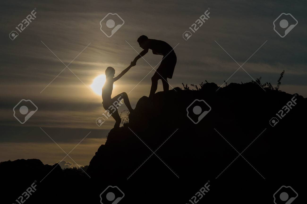 Silhouette of two boys helped pull together climbing - 51456554
