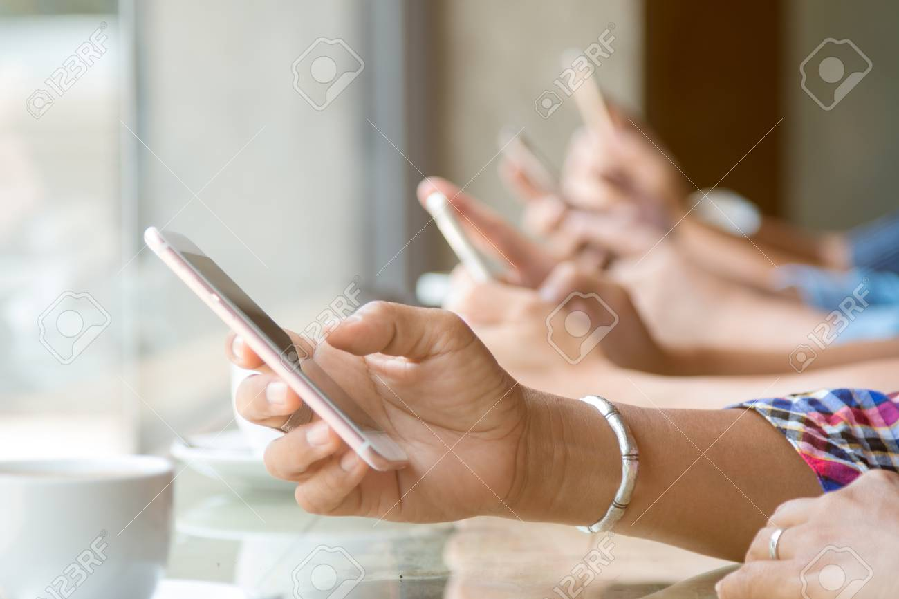 Close up of four people hand holding mobile phone and using internet in coffee shop with warm light flare - 84528317