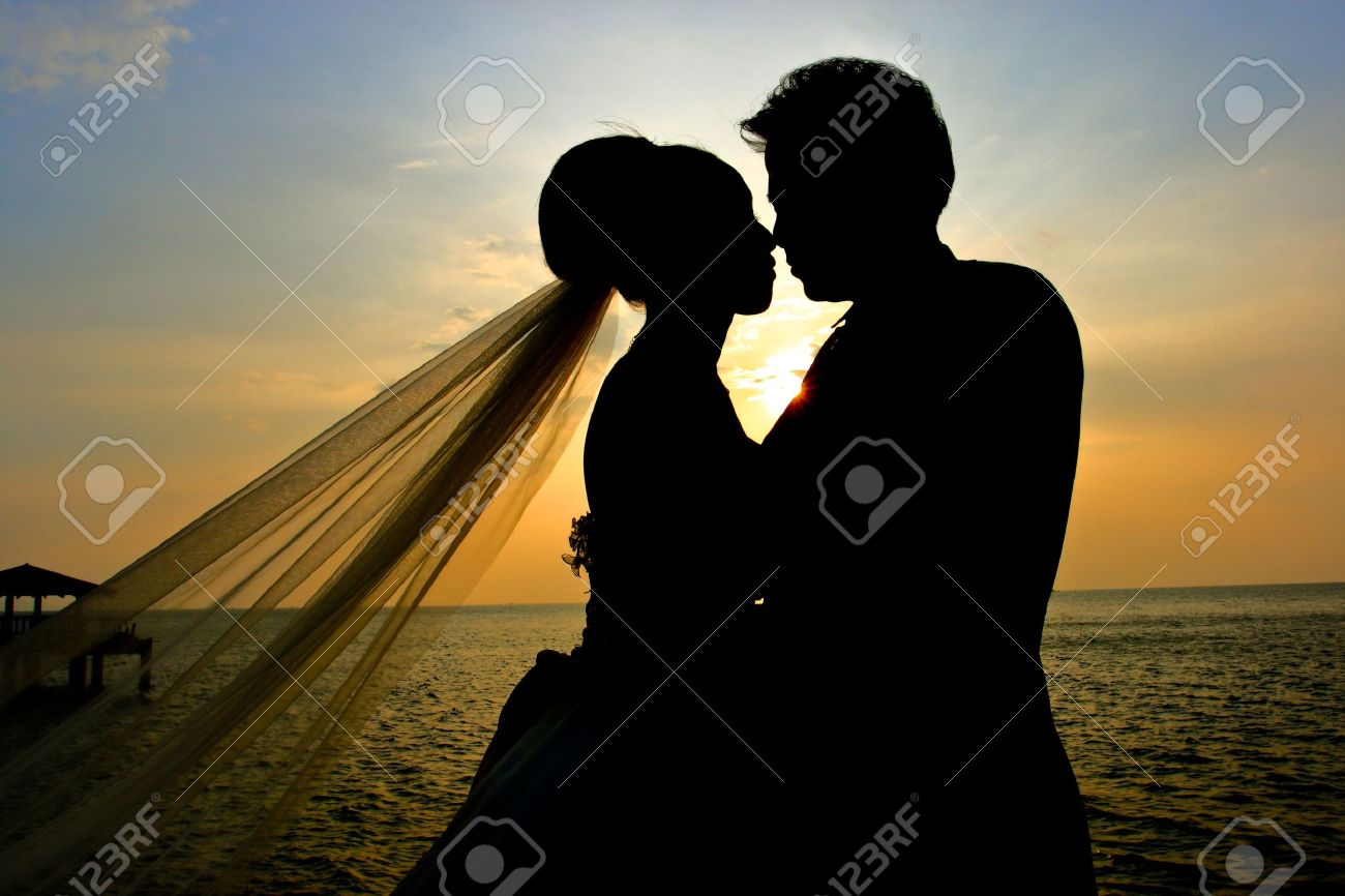 Romantic silhouette of wedding couple at sunset Stock Photo - 8687117