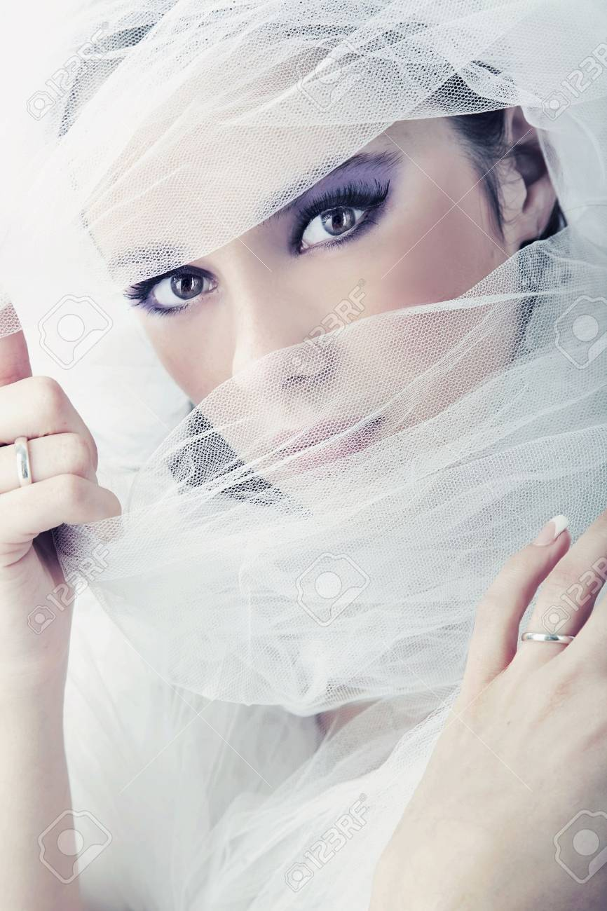 Young brunette beauty or bride, behind a white veil Stock Photo - 8944415