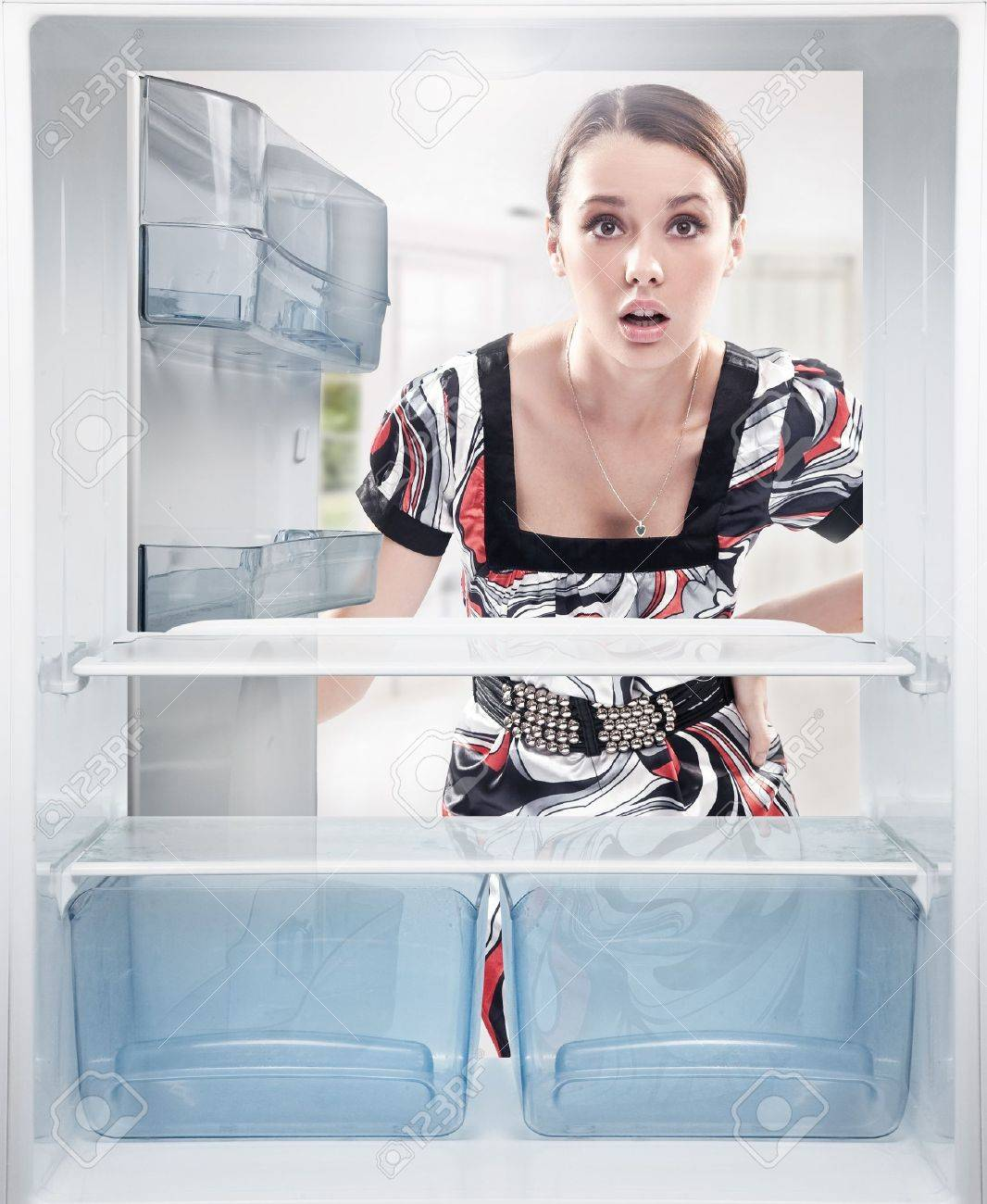 Young woman looking on empty shelf in fridge. Stock Photo - 9068061