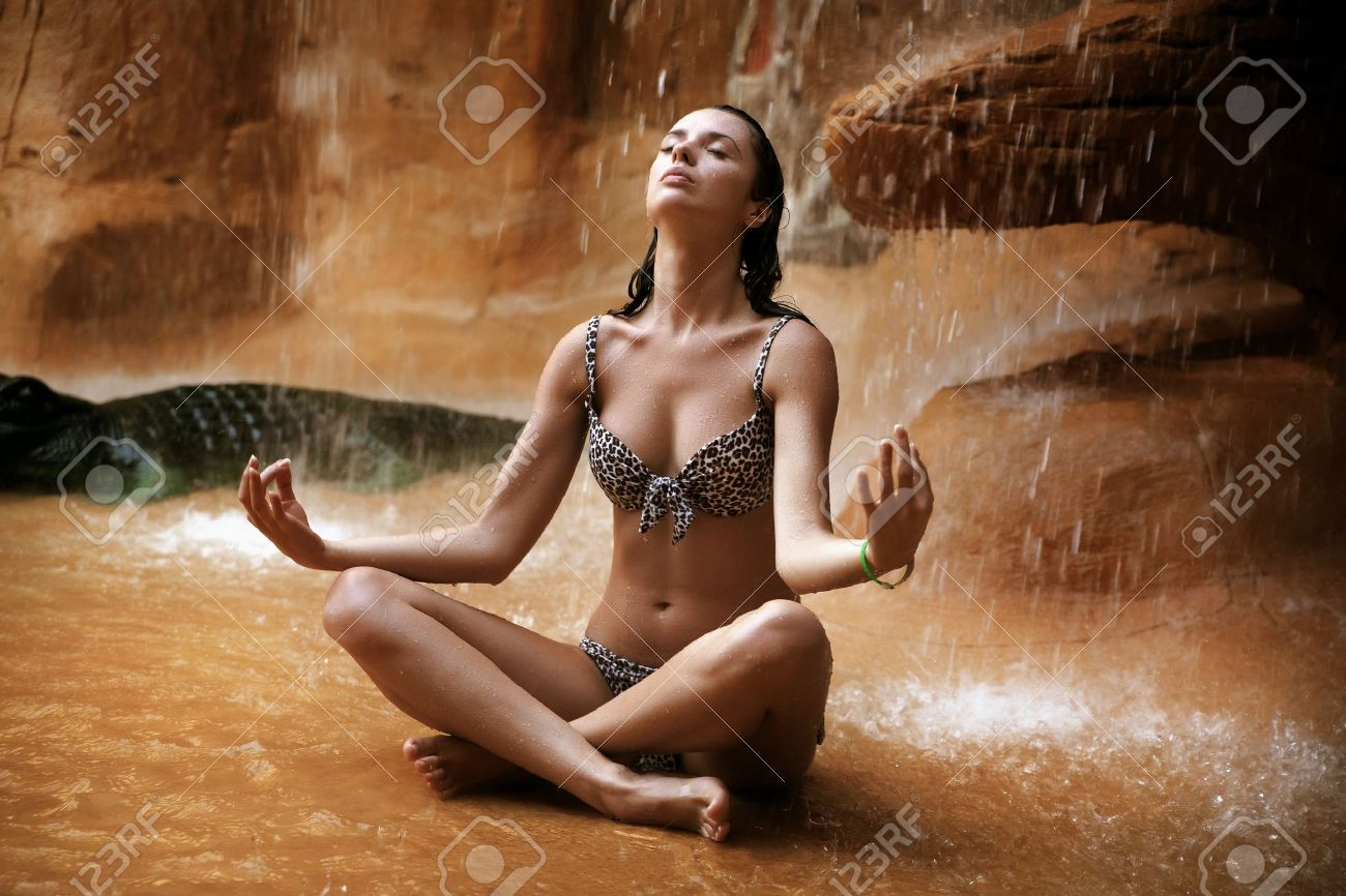 Young woman doing yoga exercise under waterfall Stock Photo - 9077724