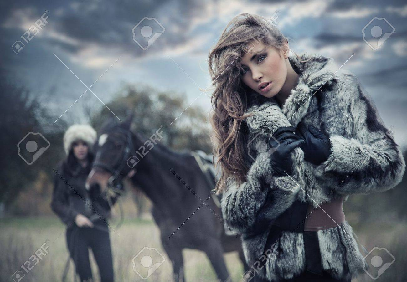 Two romantic female models posing with a horse Stock Photo - 9078233