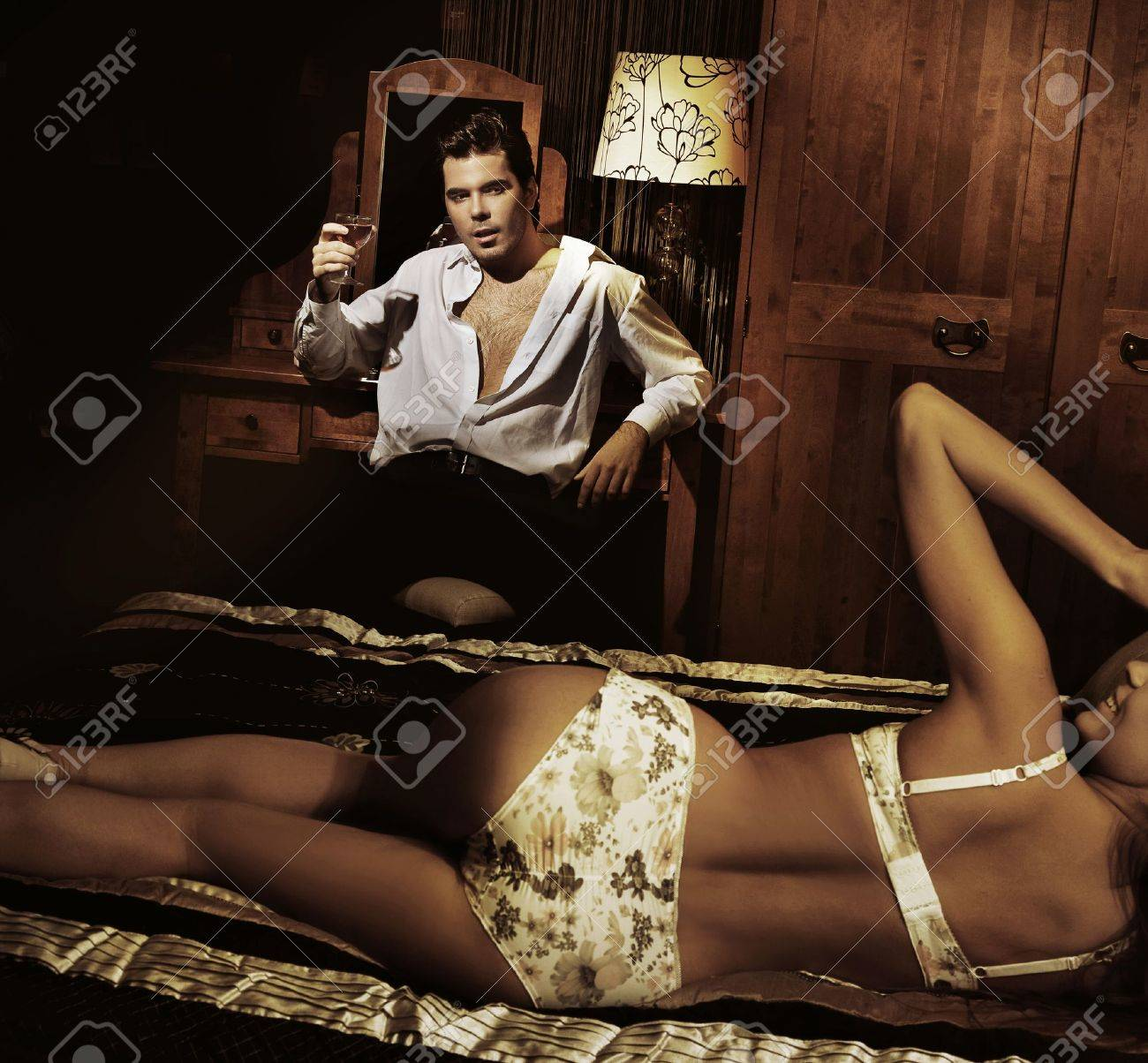 Handsome man with glass of wine with smiling girl in lingerine Stock Photo - 9336649
