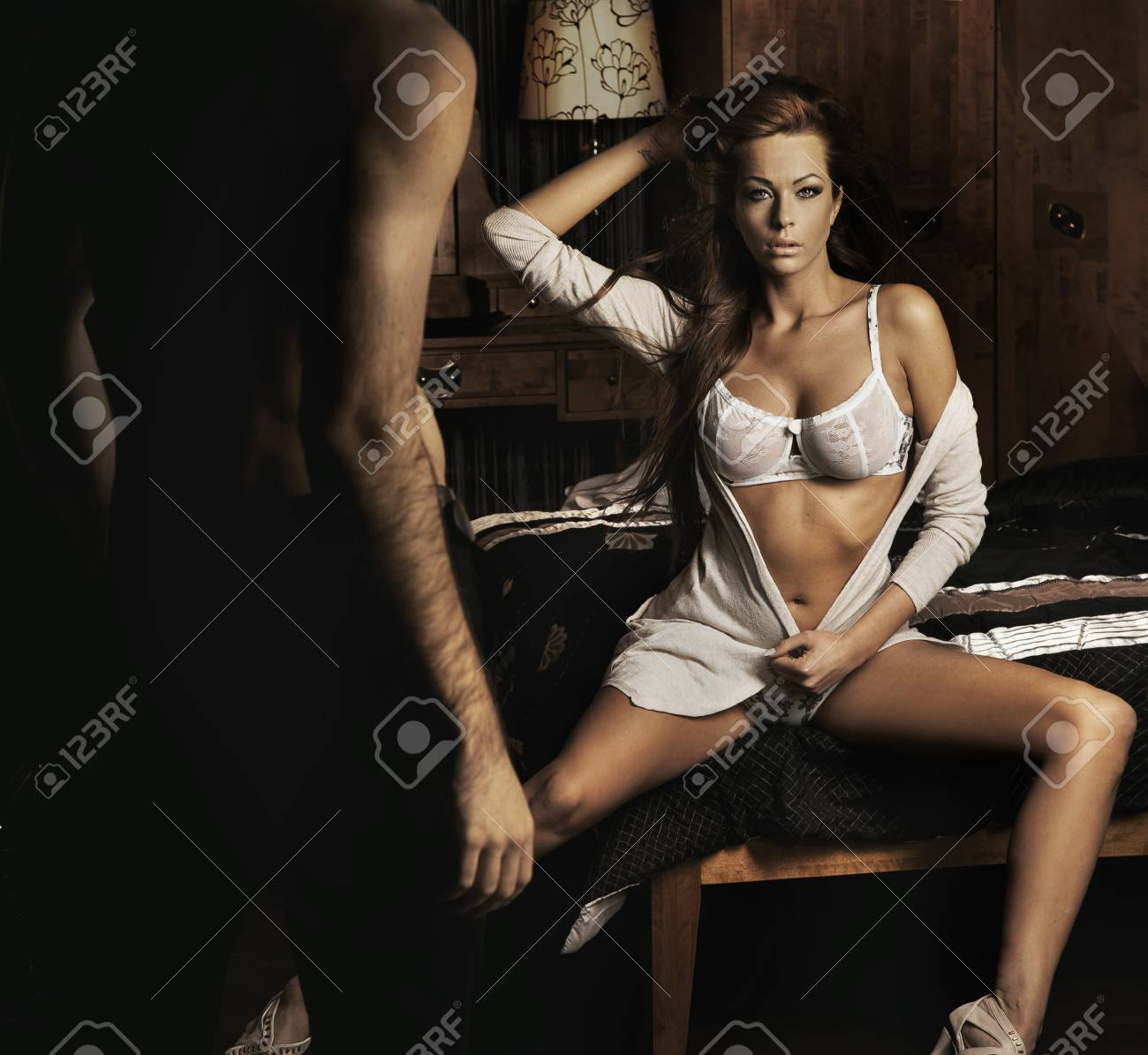 Amazing young sexy brunette sitting on the bed Stock Photo - 9316518