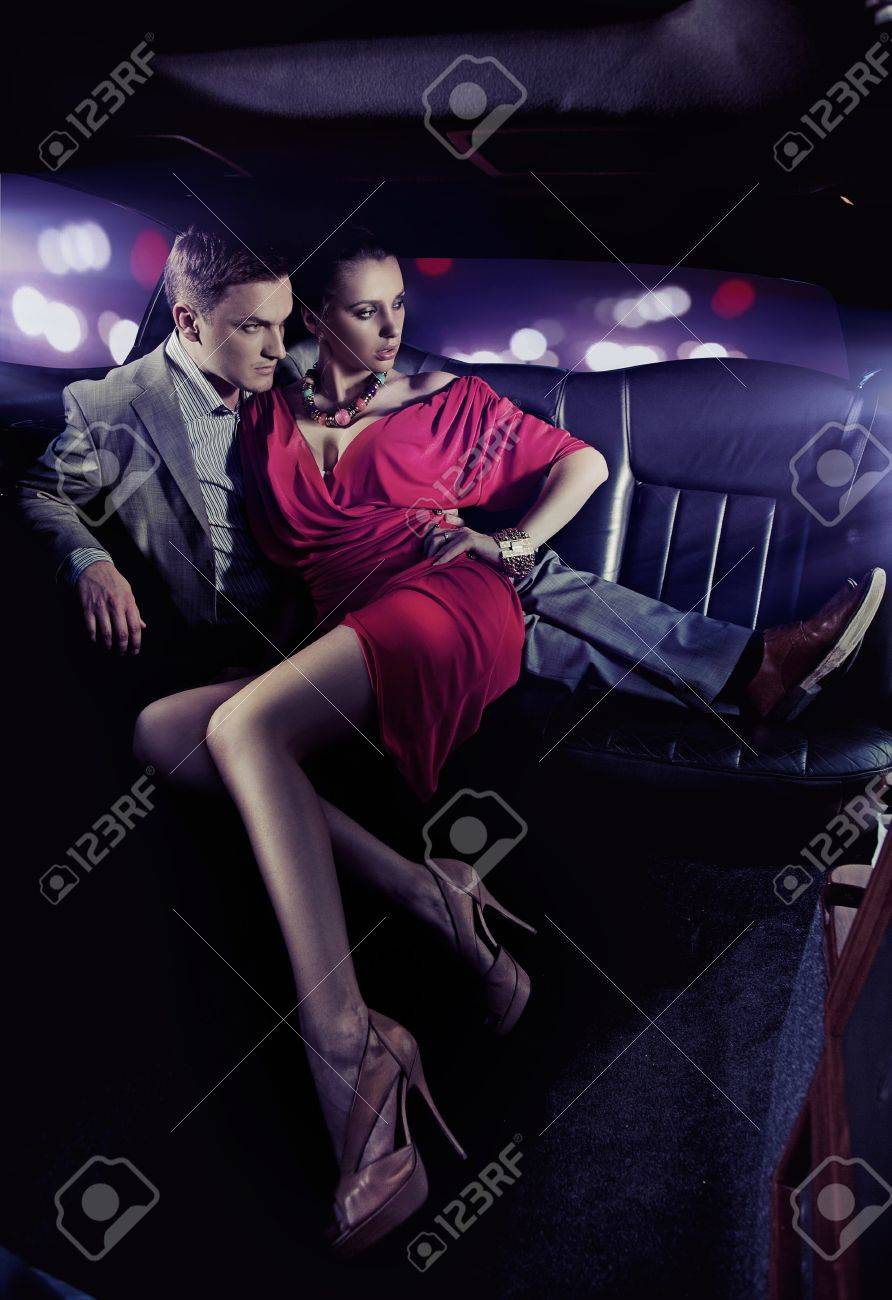 Handsome couple hugging in a luxury limousine - 9941640