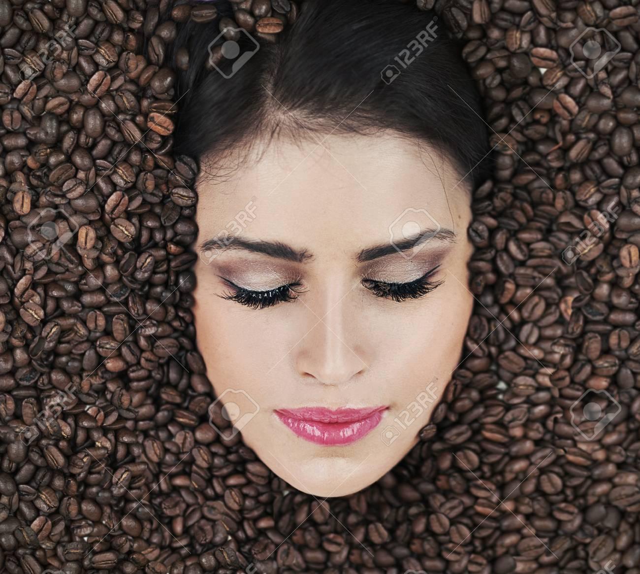 Beautiful face among coffee beans Stock Photo - 15865179