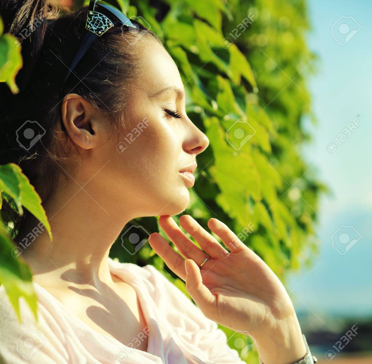 Attractive young ladyleaning on plant fence Stock Photo - 21553340