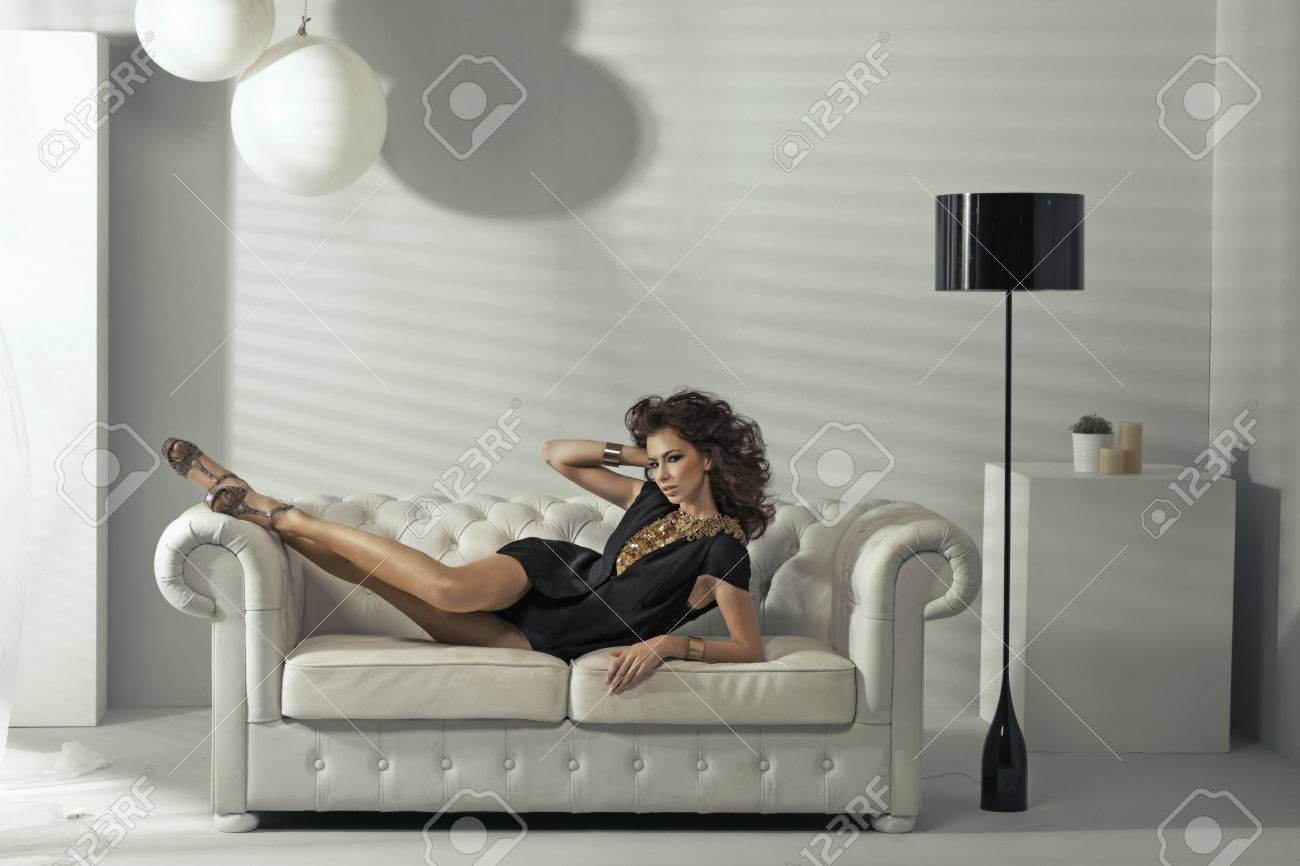 Sensual brunette lady lying at luxury white couch Stock Photo - 25321003