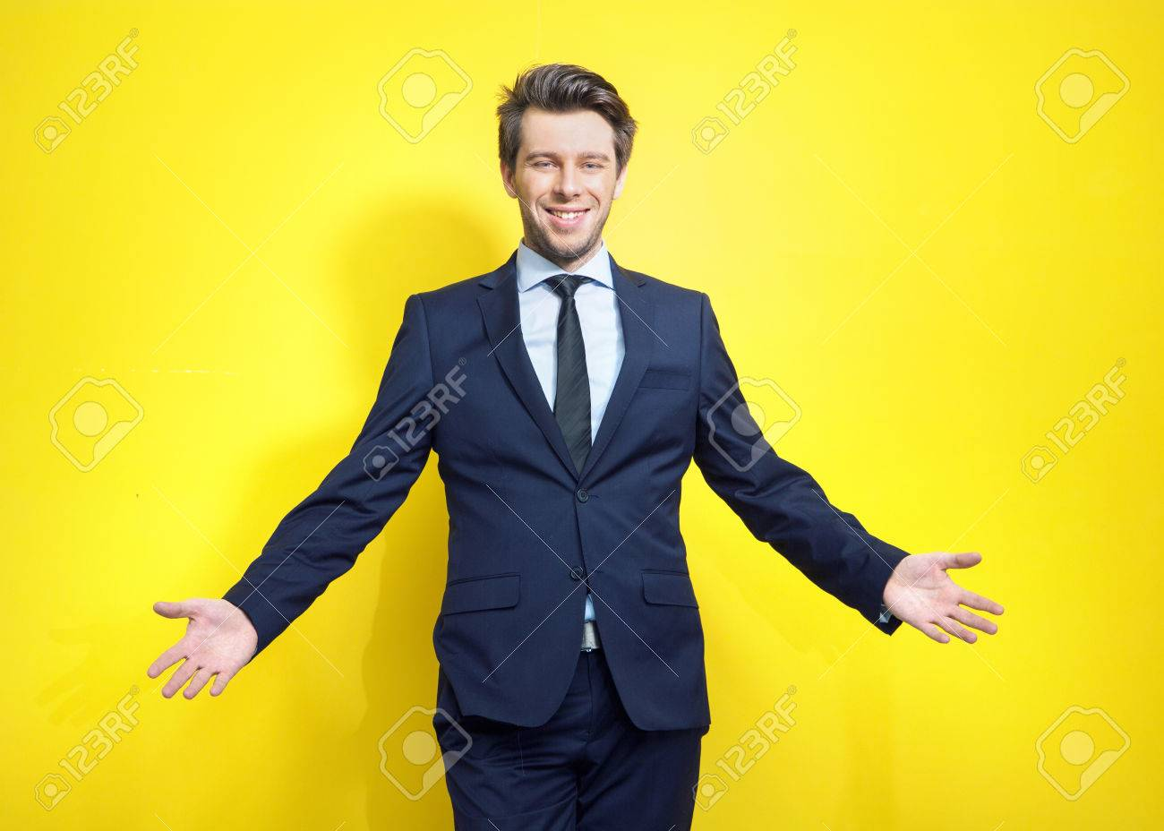 Friendly and handsome young businessman in open pose