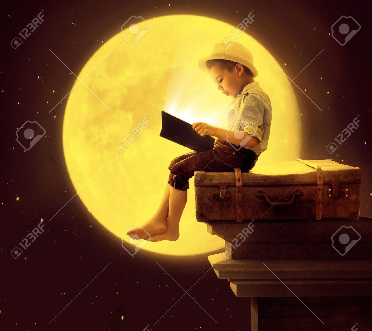 Bambino sveglio che legge un libro al chiaro di luna Archivio Fotografico - 42115690