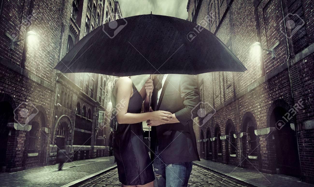 Coppie allegre nascondendosi sotto l'ombrello Archivio Fotografico - 42115417