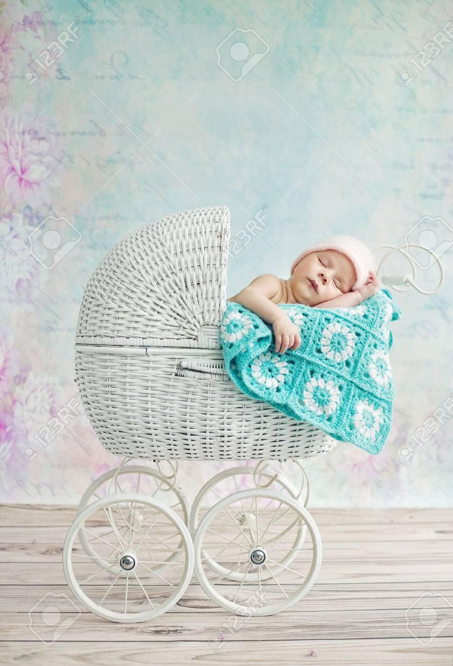 Carino bambino che dorme nella carrozzina di vimini Archivio Fotografico - 47728375