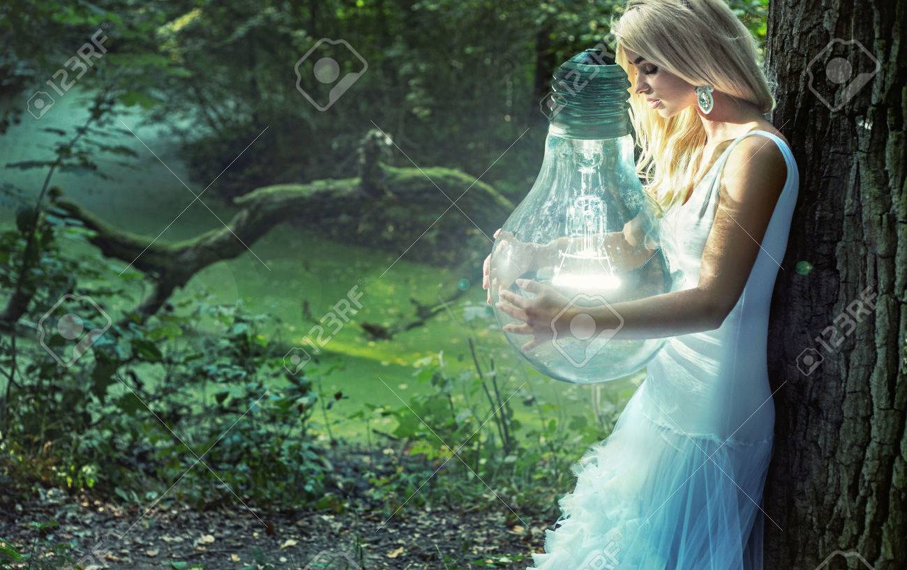 Stunning blond woman holding huge lightbulb - 50324708