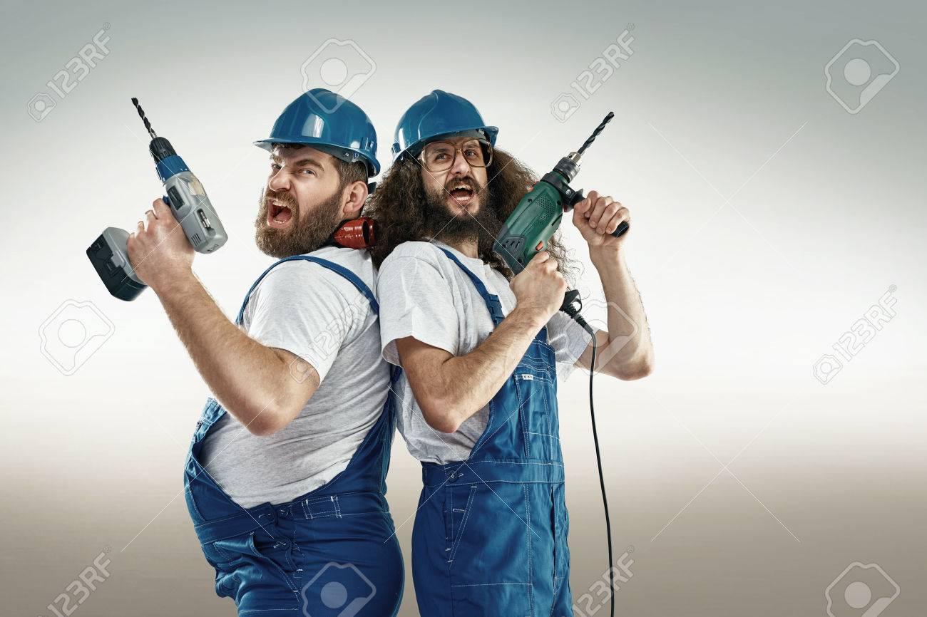Funny portrait of two cheerful craftsmen Archivio Fotografico - 55095644