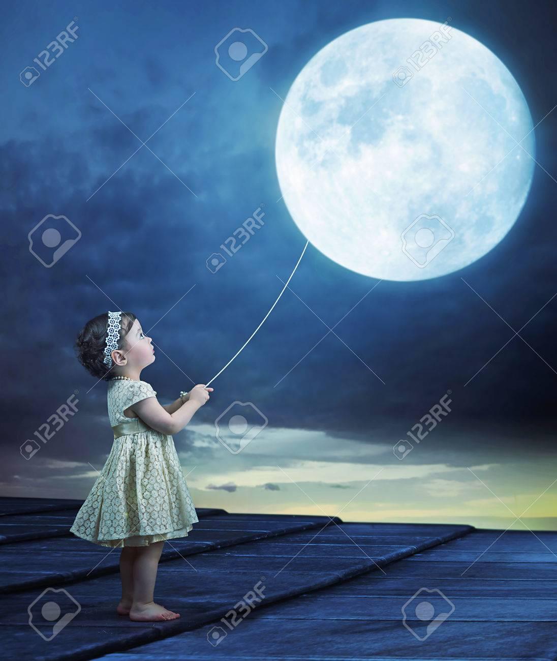 conceptual image of a cute baby holding a moon balloon stock photo