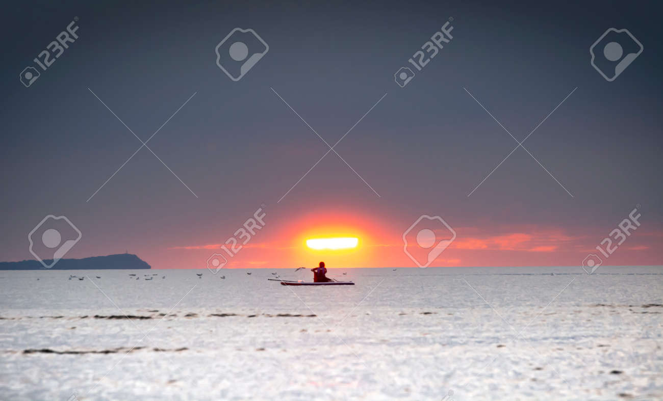 Silhouette of the girl on a surfboard at sunset - 164447672