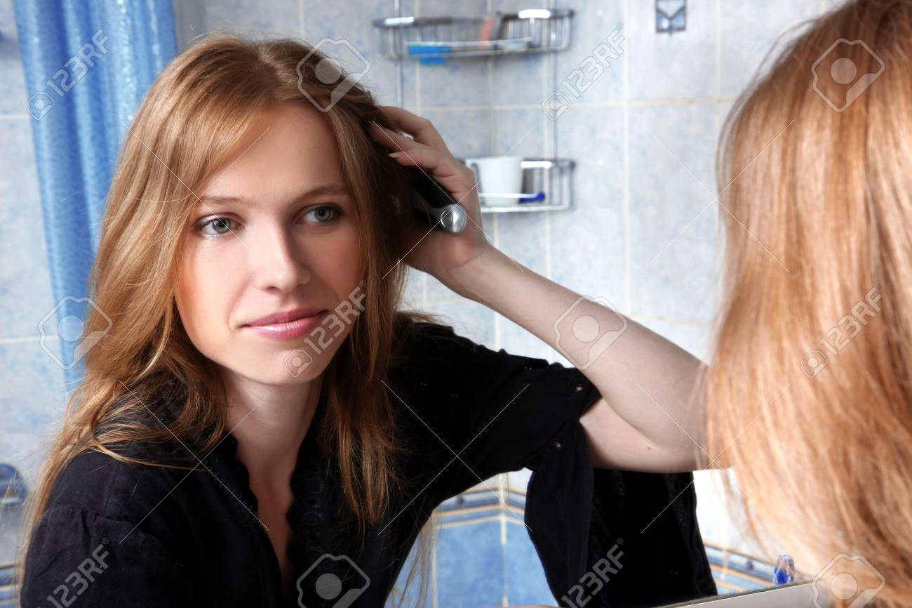 young woman in bath at front of a mirror correcting hairs Stock Photo - 16049487