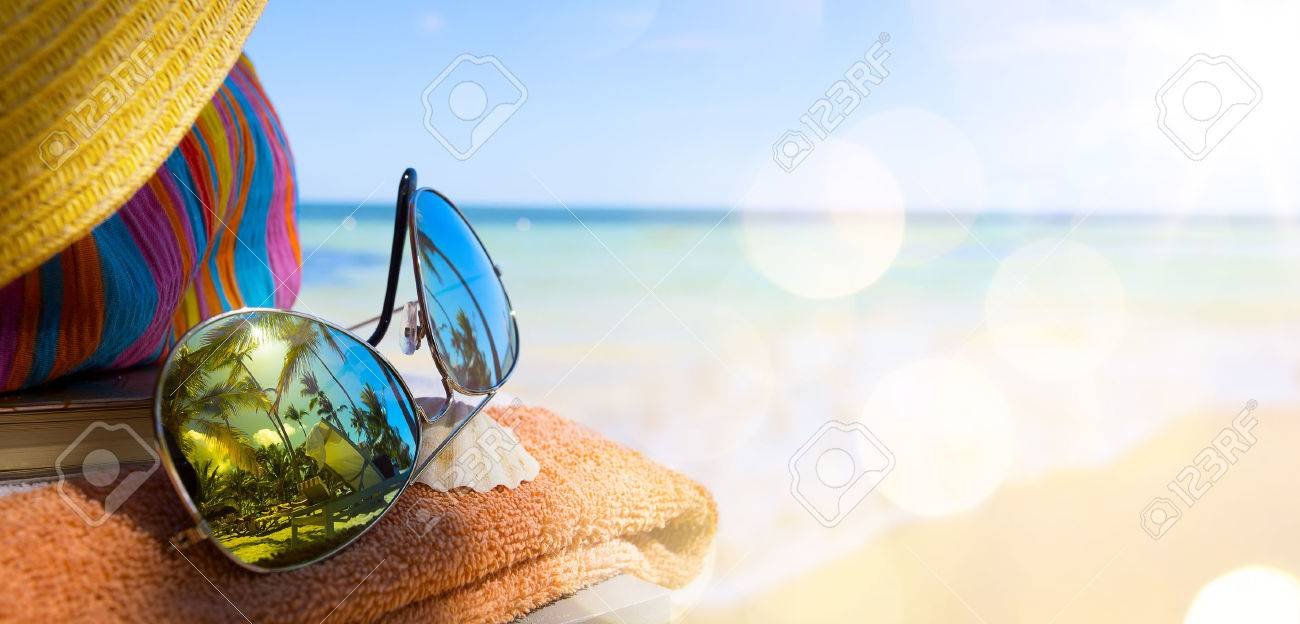 Straw hat, bag and sun glasses  on a tropical beach Stock Photo - 39582554