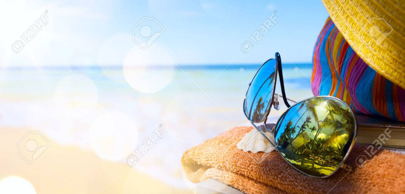 Straw hat, bag and sun glasses  on a tropical beach Stock Photo - 40063073
