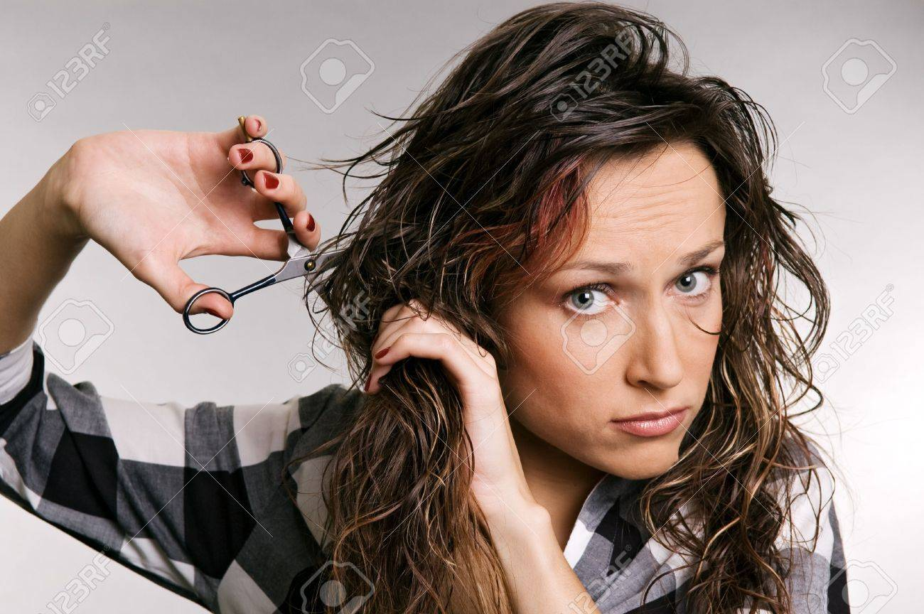 beautiful woman cutting her hair over grey background Stock Photo - 3704648