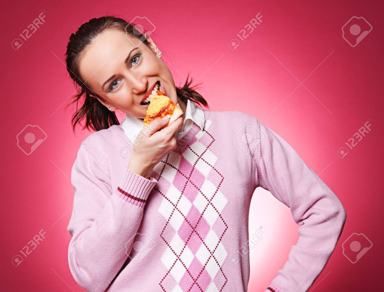 casual woman eating pizza over pink background Stock Photo - 4189664