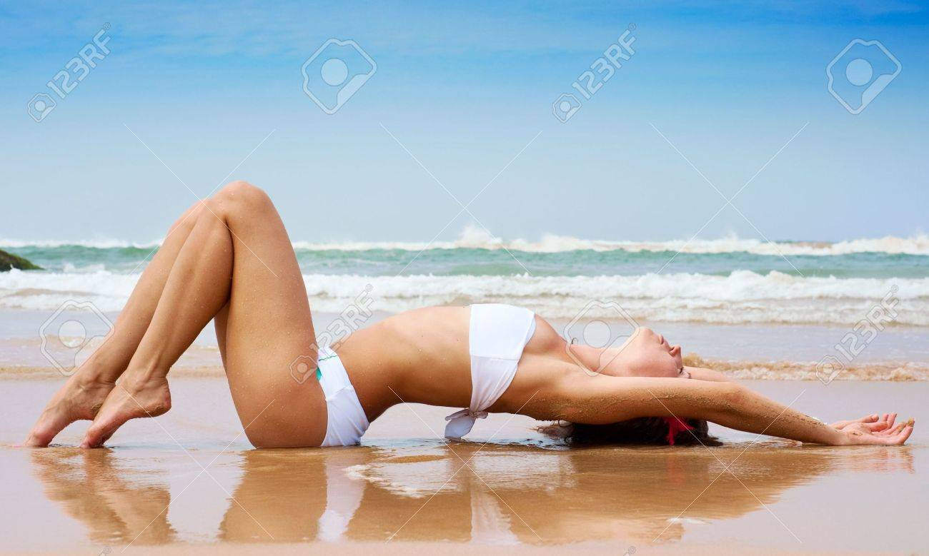 beautiful woman lying on the wet sand against ocean and blue sky Stock Photo - 6410287