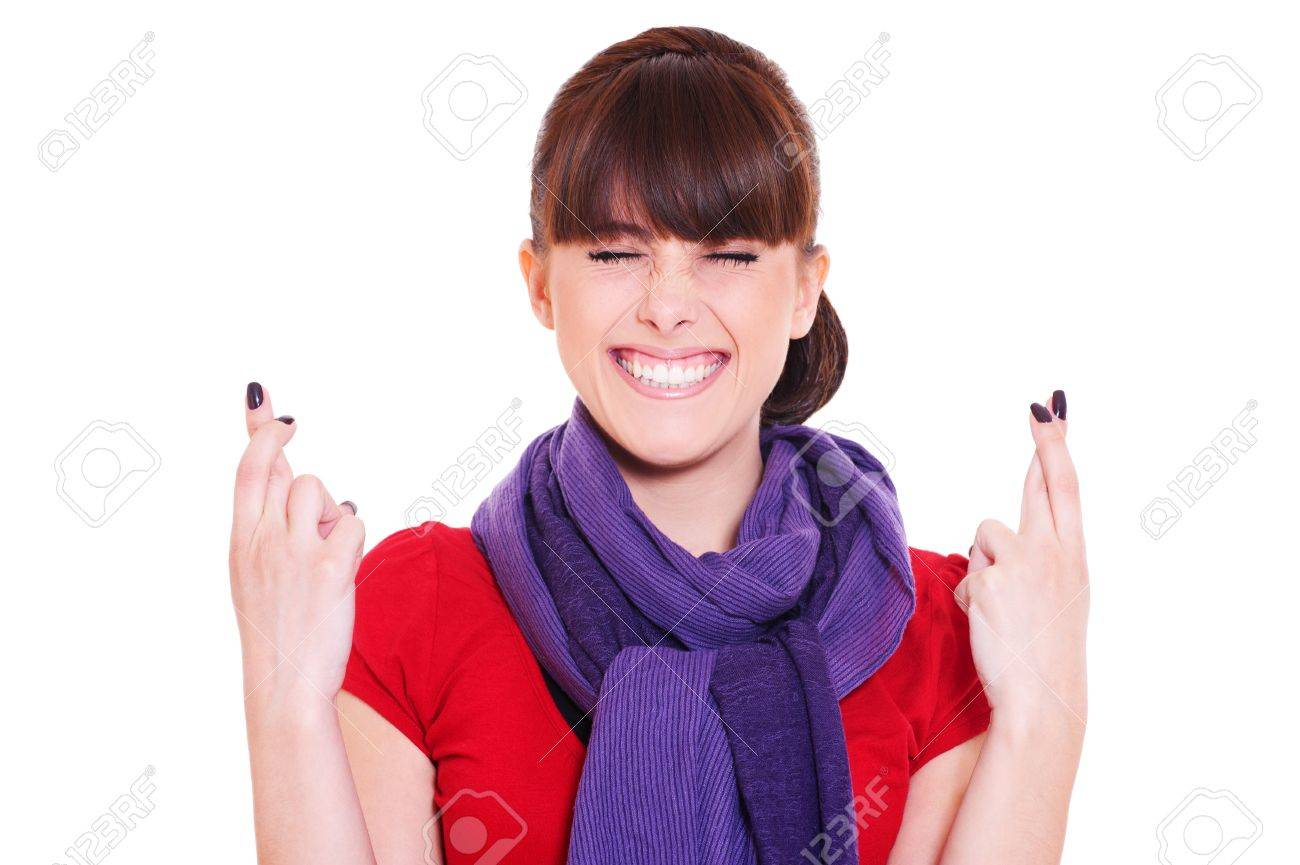 young smiley woman hoping hard with fingers crossed against white background Stock Photo - 9763851