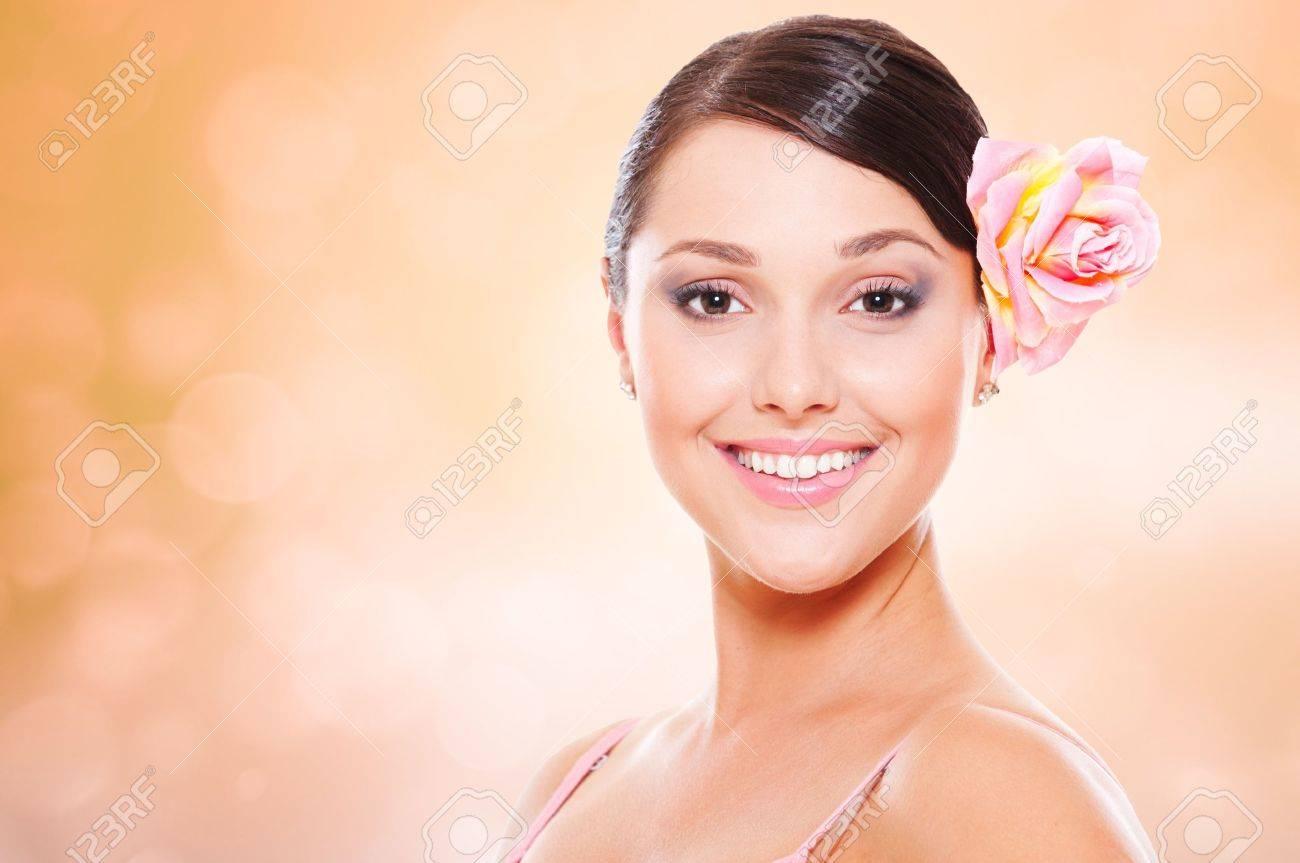 portrait of happy smiley model with rose in hair Standard-Bild - 14158135