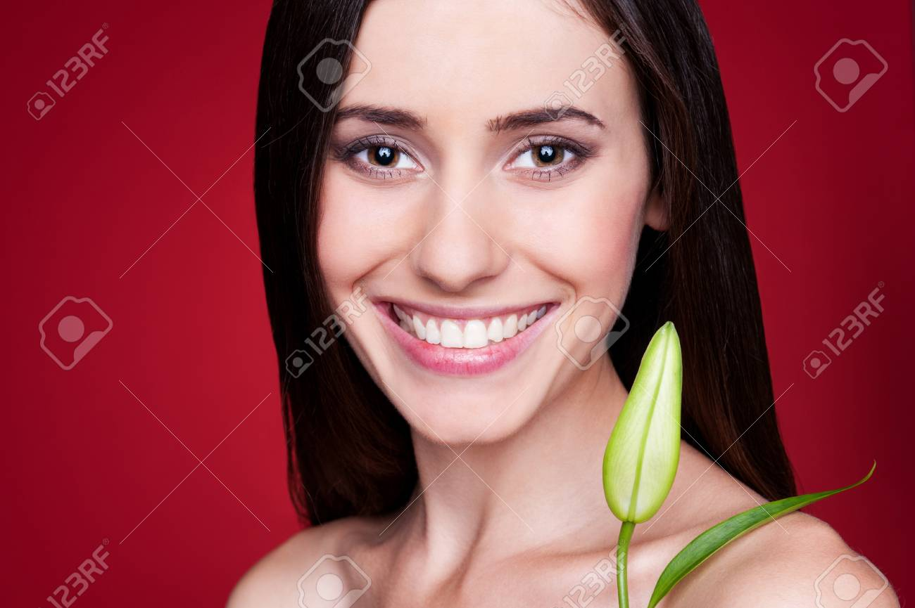 portrait of alluring young woman with flower bud. studio shot over red background Stock Photo - 14748929