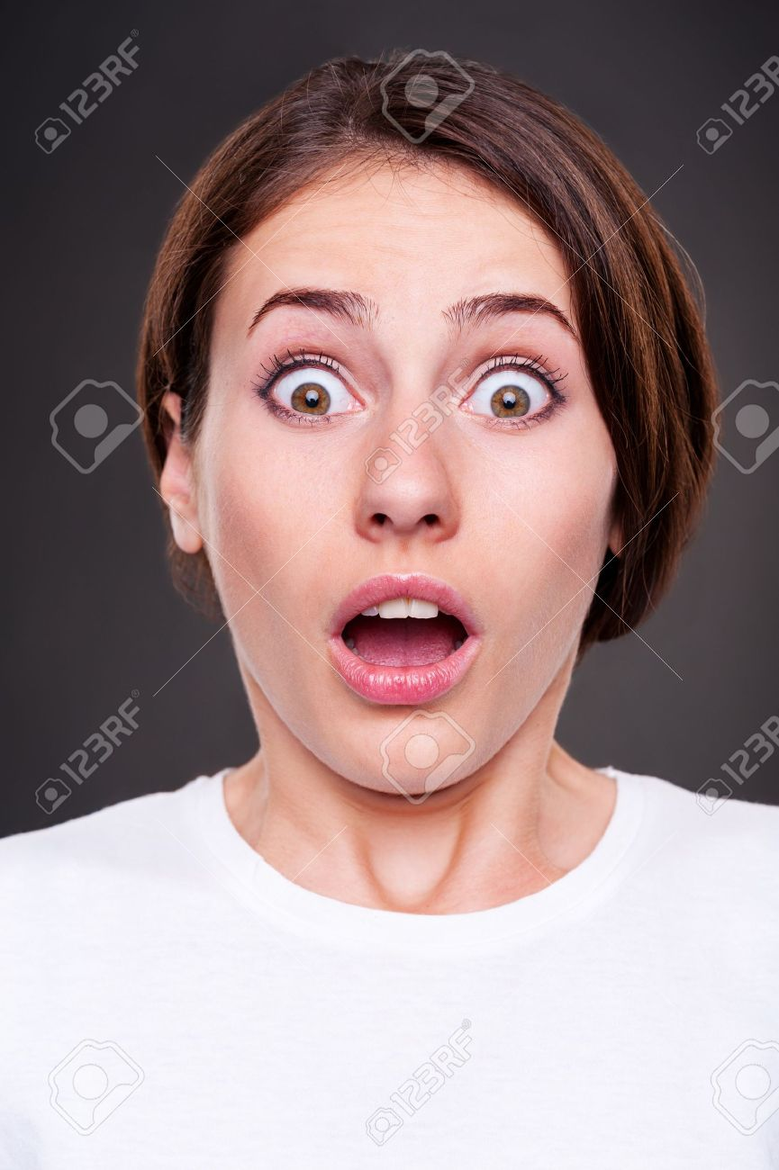 portrait of surprised woman with open mouth over dark background Stock Photo - 15038187