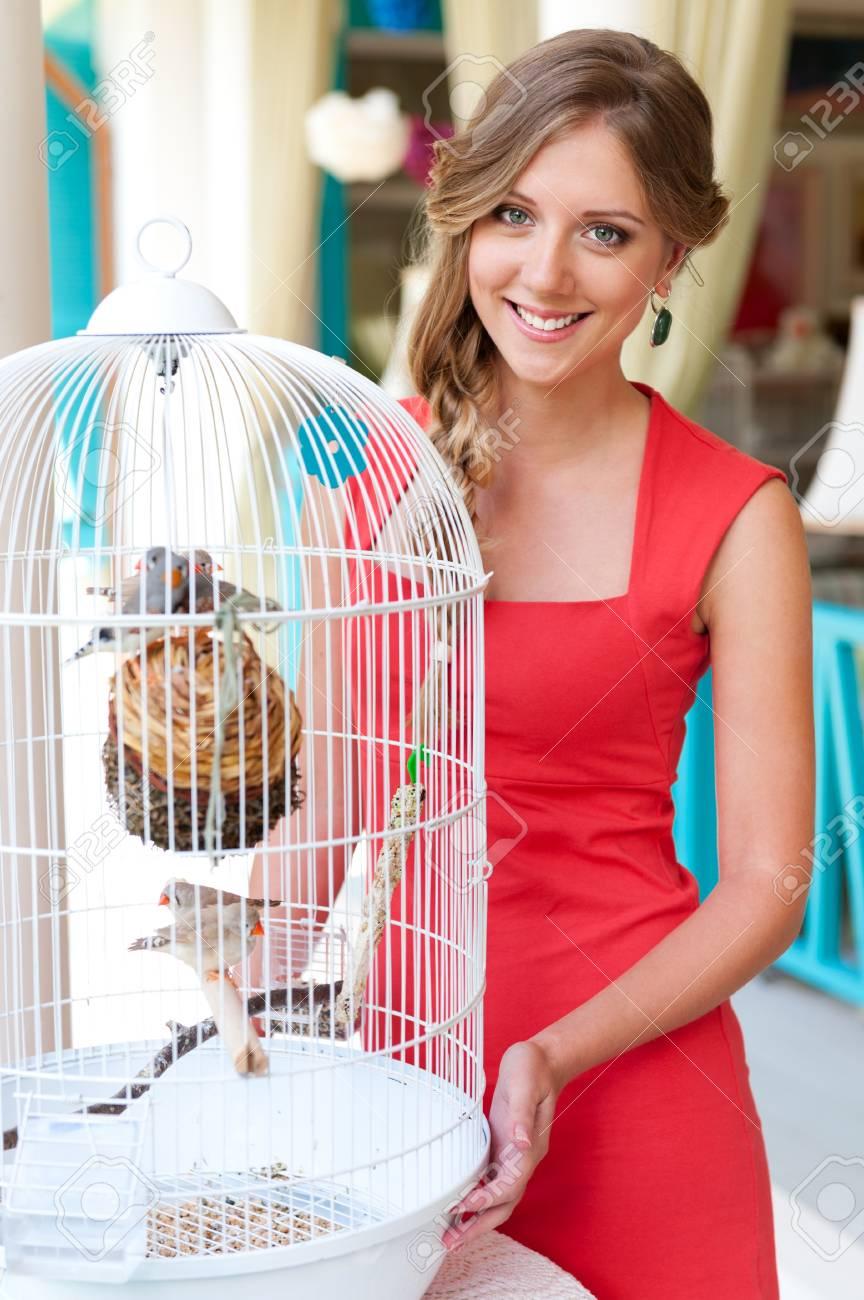 Joven Y Bella Mujer De Pie Vestido Rojo Cerca De Jaula Con Pájaros ...