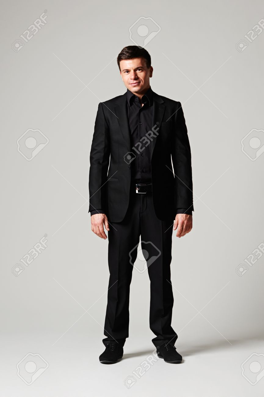 Full Length Portrait Of Stylish Man In Black Suit Over Grey