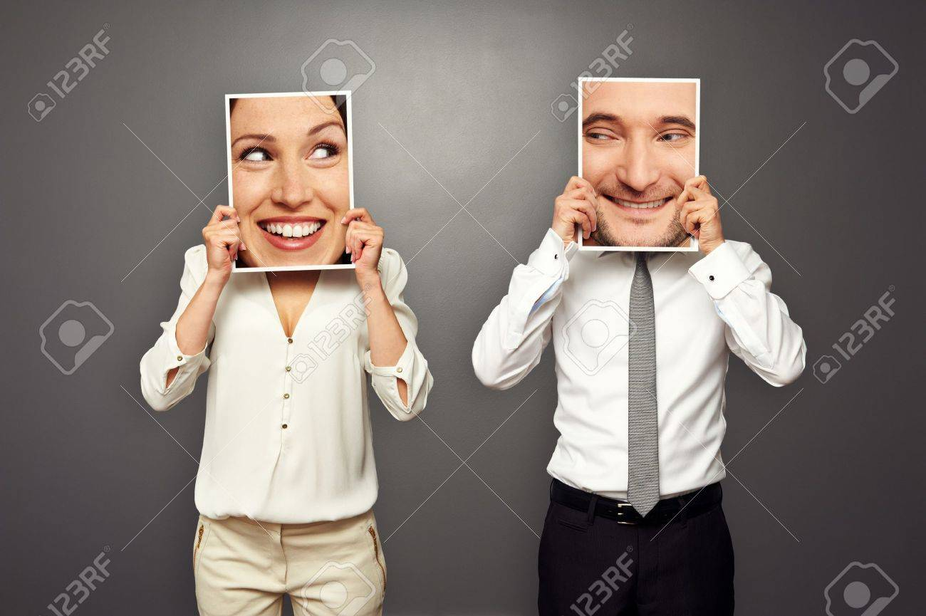 man and woman holding smiley faces. concept photo over dark background Stock Photo - 19377889