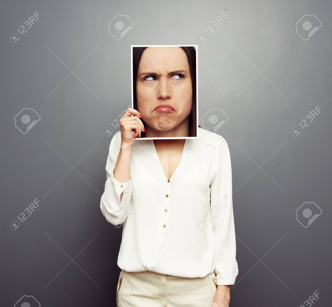 young woman covering image with big pensive face. concept photo over grey background Stock Photo - 19377963