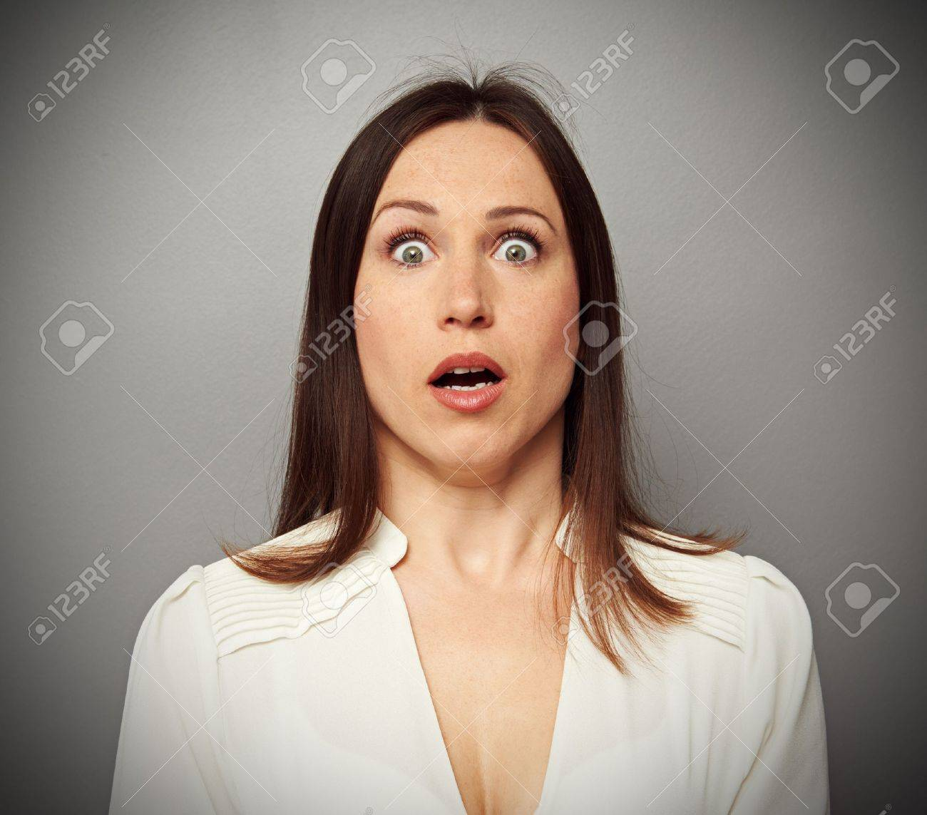 frightened woman looking at camera over dark background - 19563364