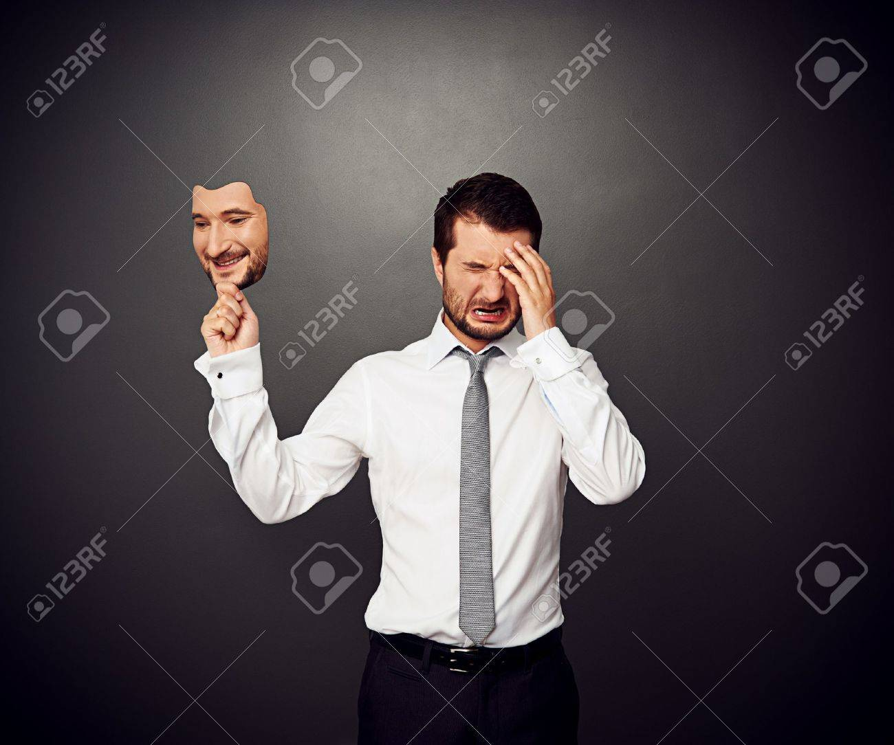 crying man holding mask with smiley face Stock Photo - 20019909