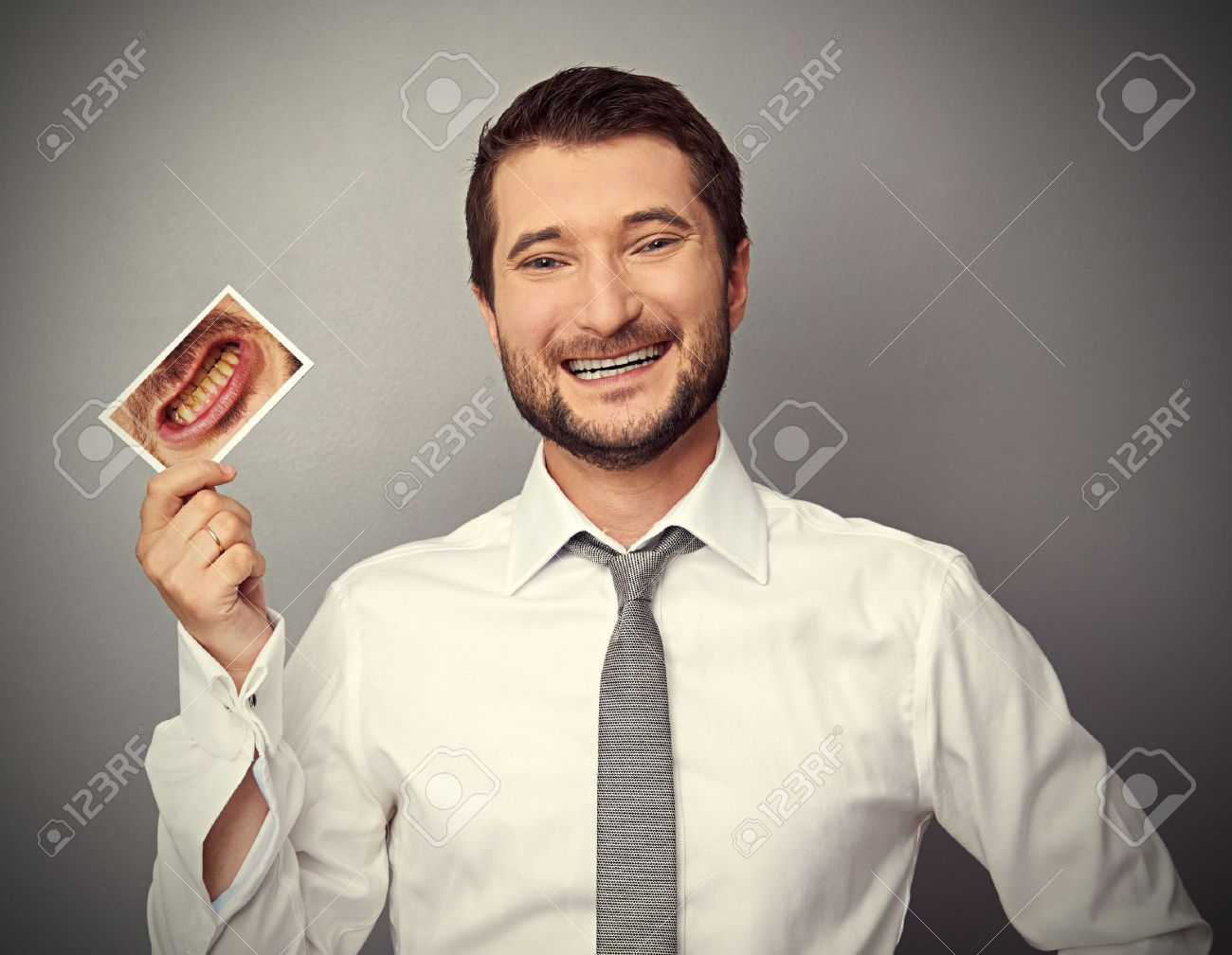 smiley healthy man holding picture with dirty yellow teeth Stock Photo - 20147165