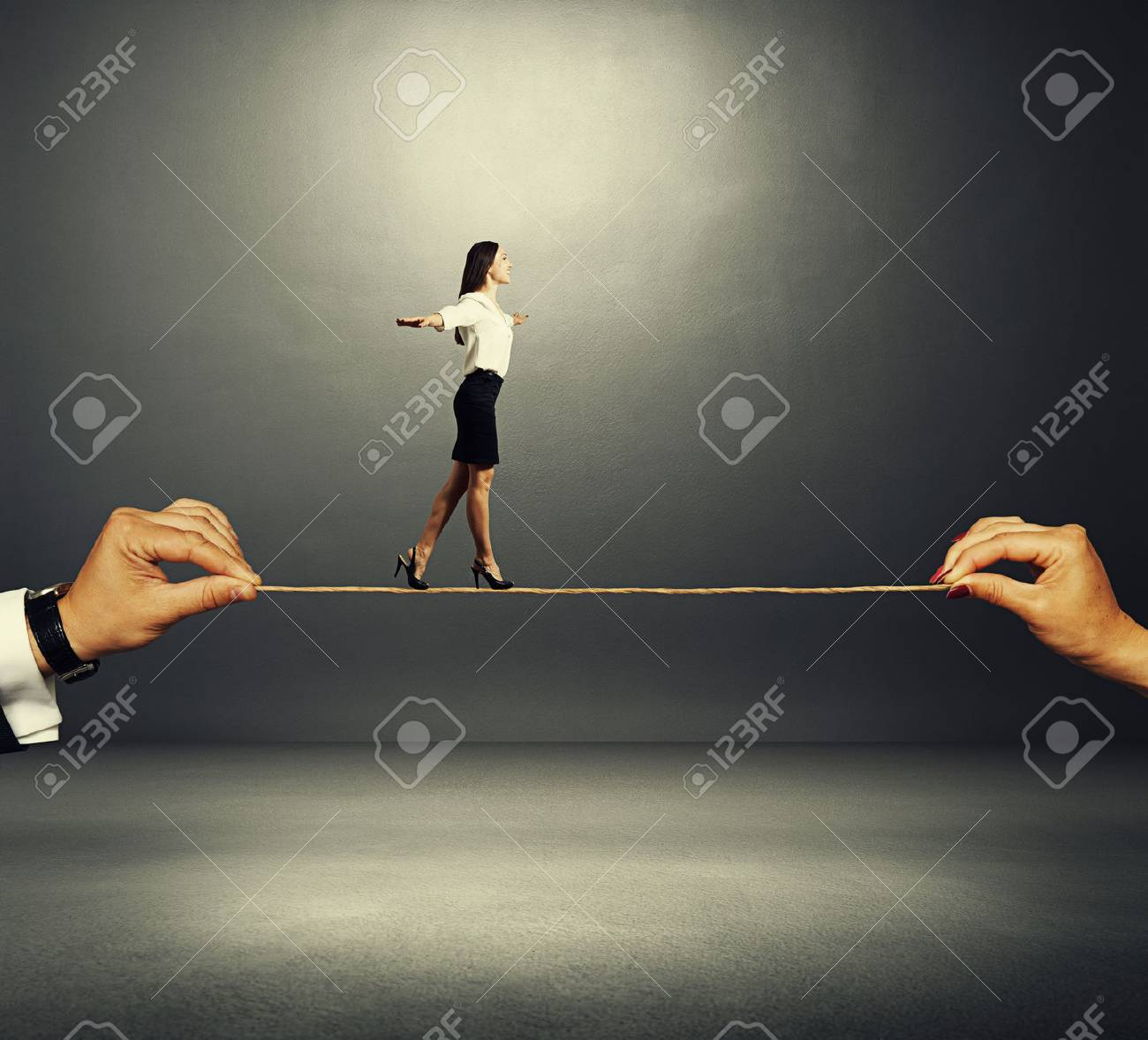 assured smiley woman walking on the rope over dark background Stock Photo - 29018736