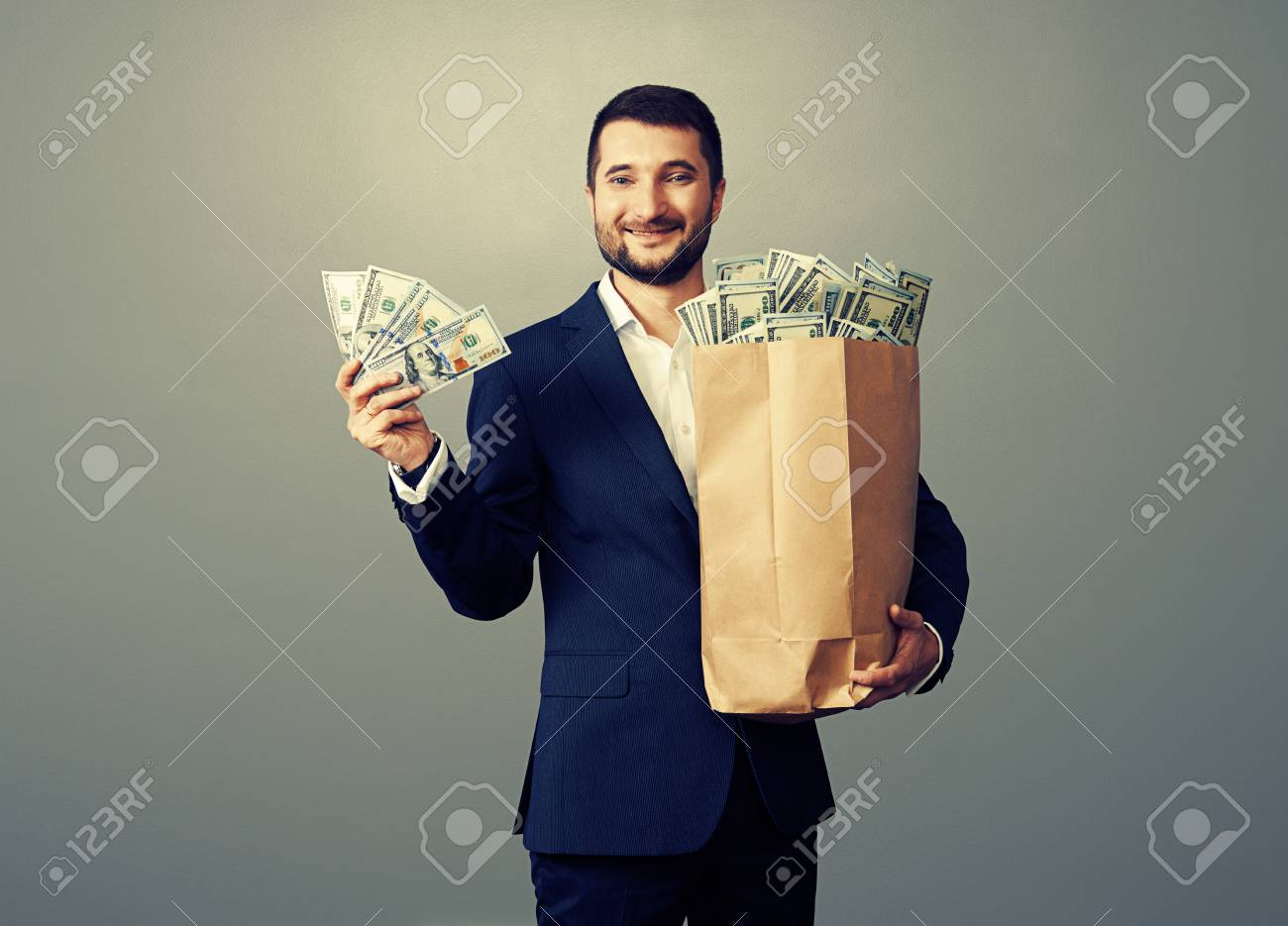 successful businessman holding paper bag with money and smiling. studio photo over grey background Stock Photo - 29619629