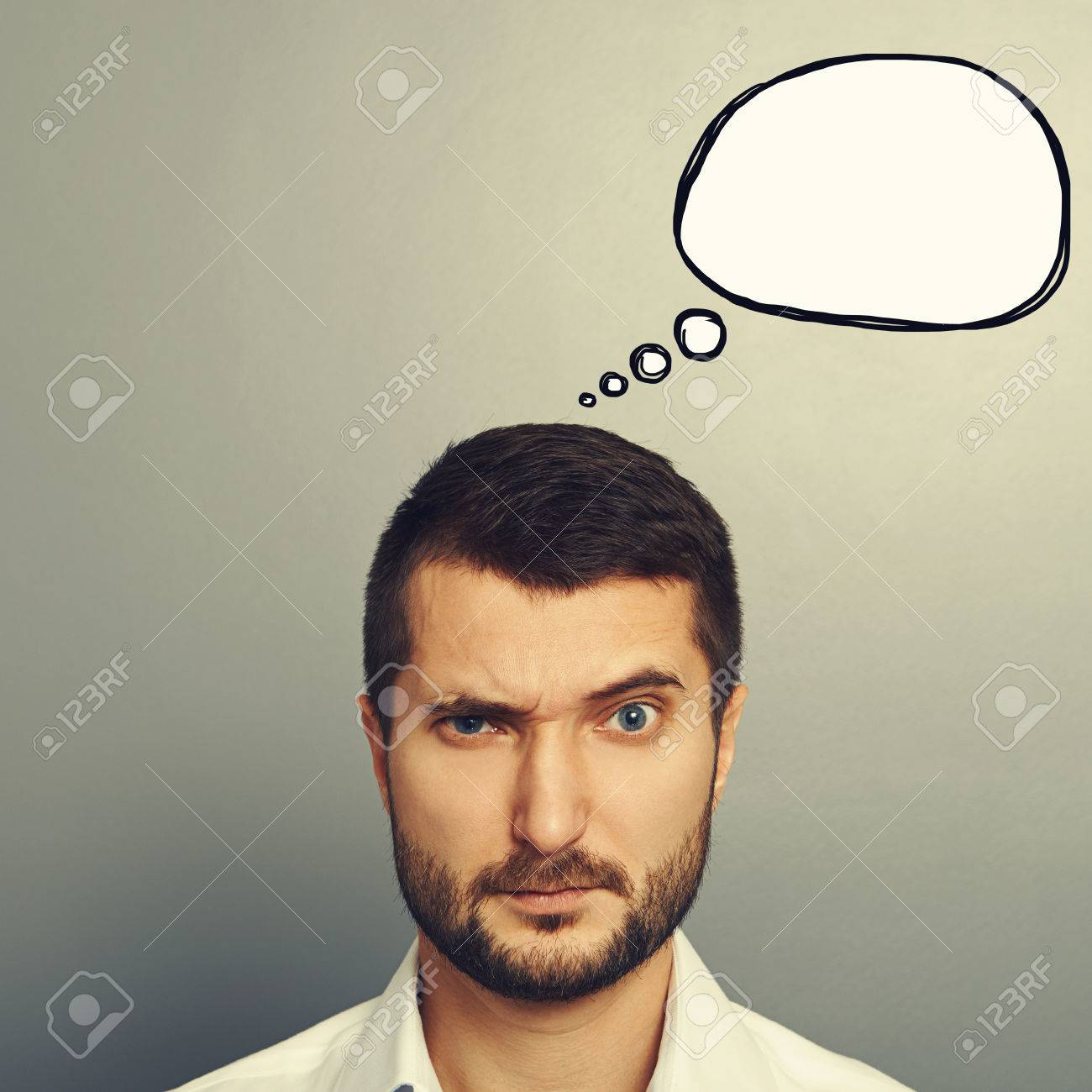 pensive man with empty speech bubble looking at camera over grey background Stock Photo - 30834582