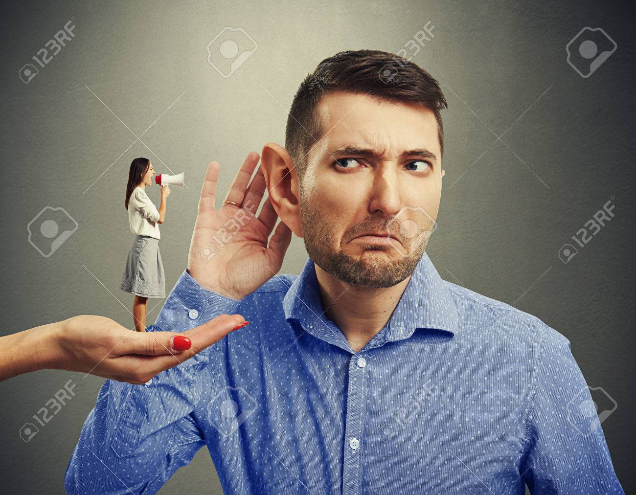 small woman standing on big female hand and screaming with megaphone at man with big ear over grey background - 38921505
