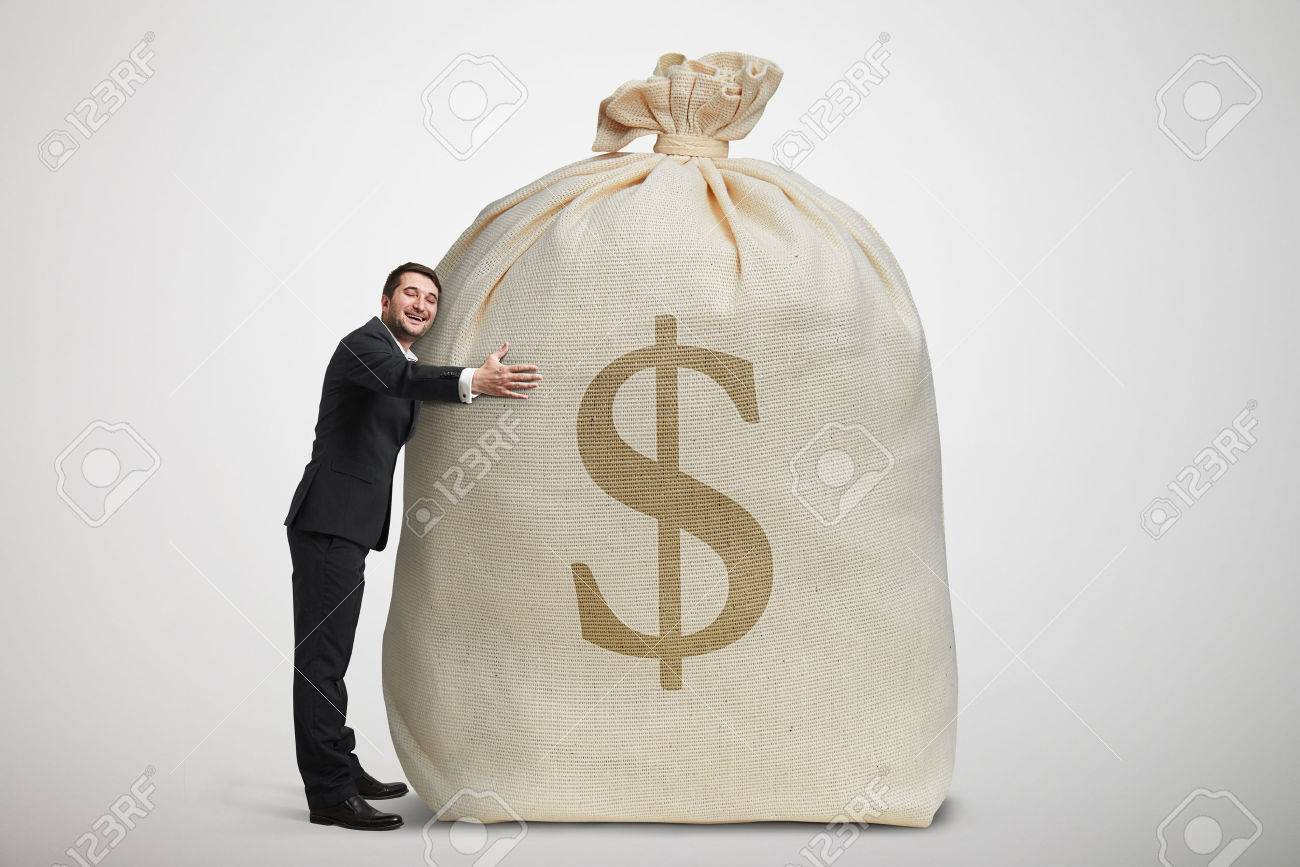happy man embracing big bag with money over light grey background - 39302590