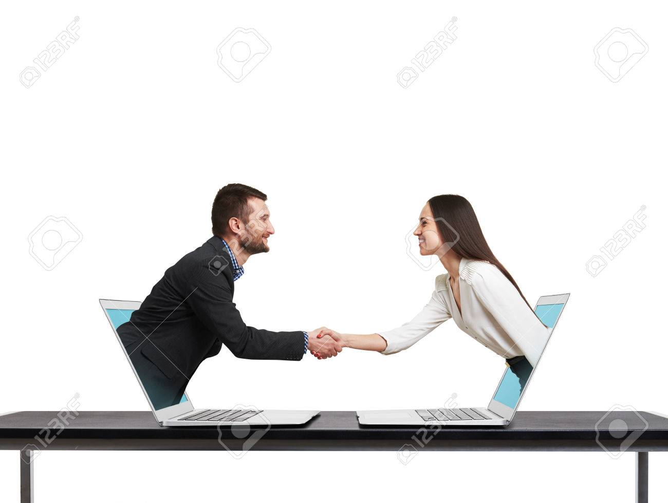 smiley businessman and businesswoman come out from laptop, shaking hands and looking at each other over white background - 39302591