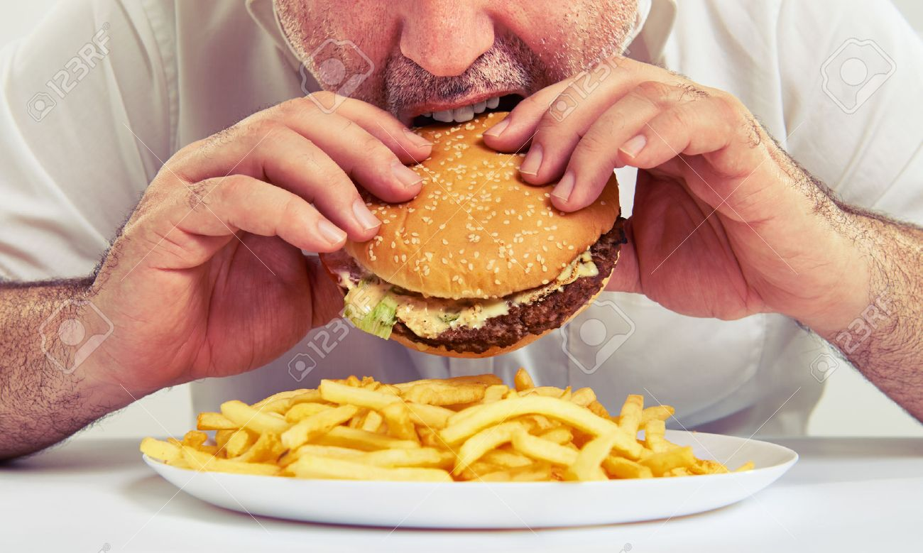 close up photo of man eating burger and french fries - 40300796