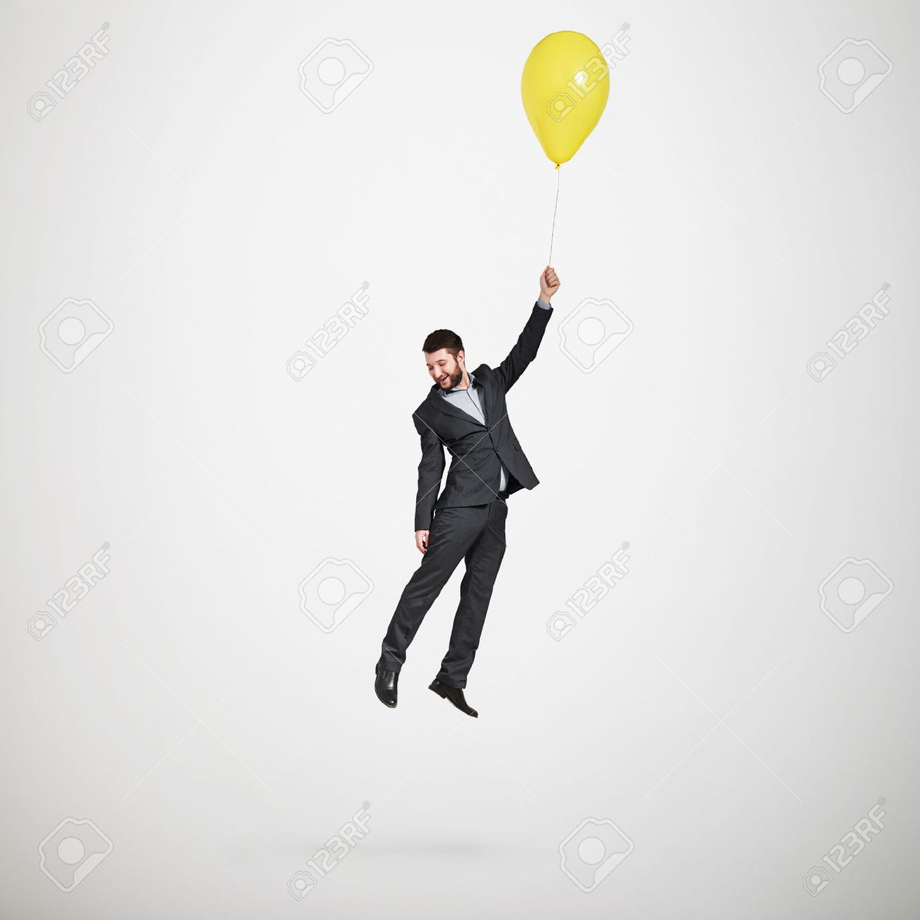 laughing man flying with yellow balloon and looking down over light grey background - 40928687